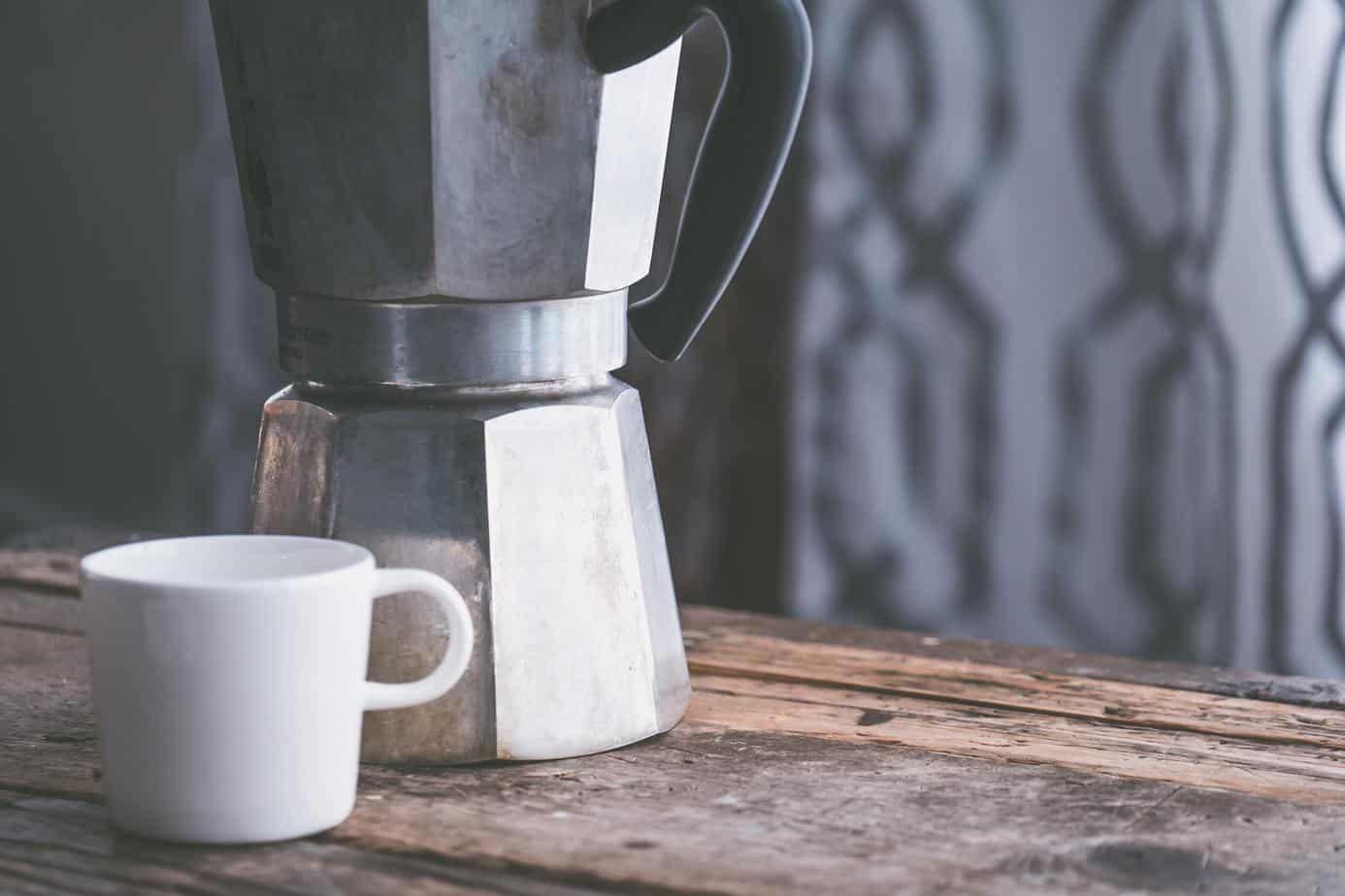 white mug beside moka pot